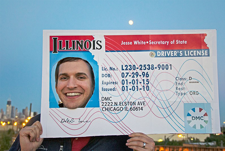 Photo of Eric West posing with his face inside a giant fake DMC Illinois Drivers License.