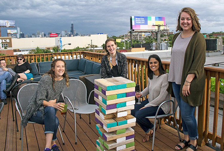 Photo of group by giant Jenga on the rooftop.