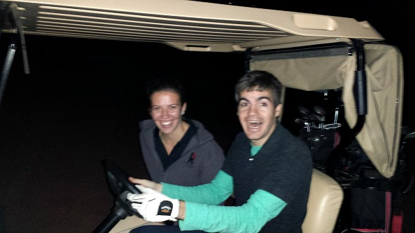 Two engineers take a ride in a golf cart.