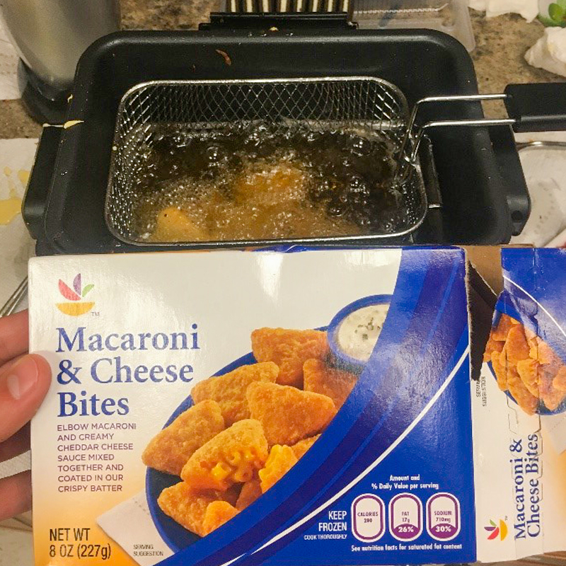 Photo of mac n cheese bites frying in the fryer.