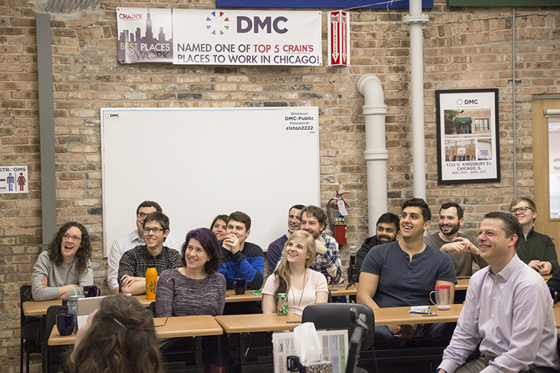 A photograph taken of DMC employees laughing at a DMC Monthly Company Meeting