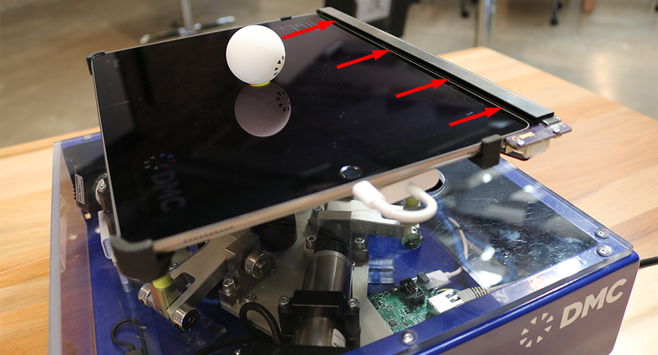 Red arrows point to the Neonode sensor on the DMC tilt table demo.