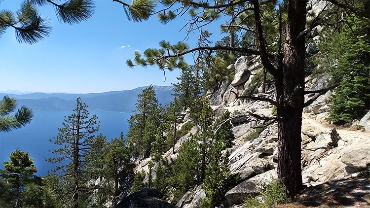 Photo from  the trail overlooking Lake Tahoe far below with Sierra Nevada mountains in the background.
