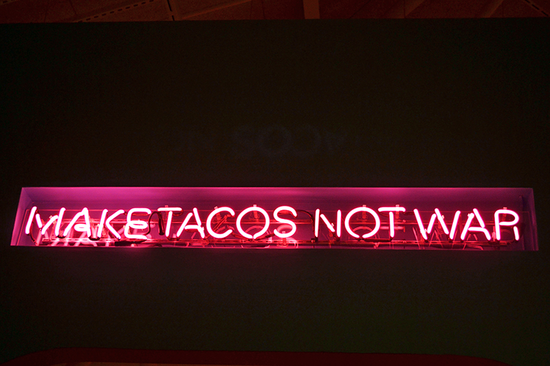 "Neon sign reading ""Make Tacos Not War"""