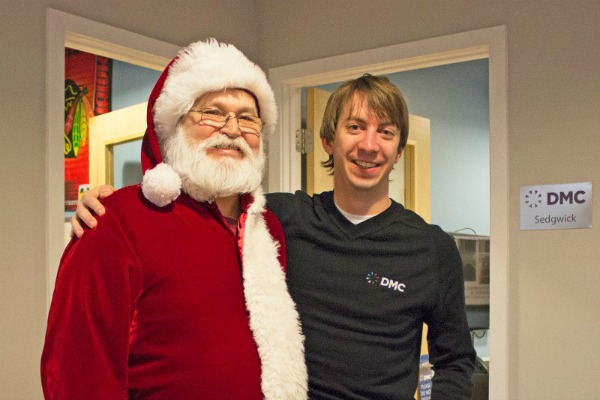 DMC engineer, Alex, smiles with Santa.